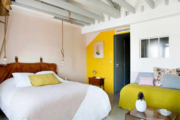 A colourful bedroom with yellow and pink walls and exposed beams