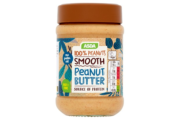 A clear tub filled with brown peanut butter and a brown lid