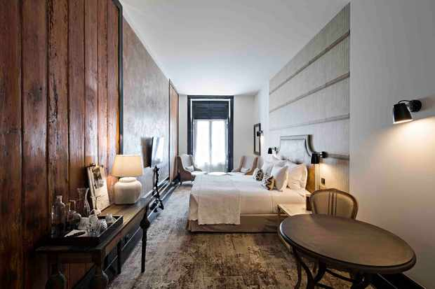 Hotel bedroom with neutral tones, a large bed, antique side table and brushed wooden floorboards