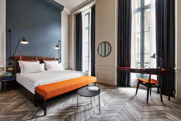 A spacious bedroom with dark blue walls, parquet flooring and an orange bench