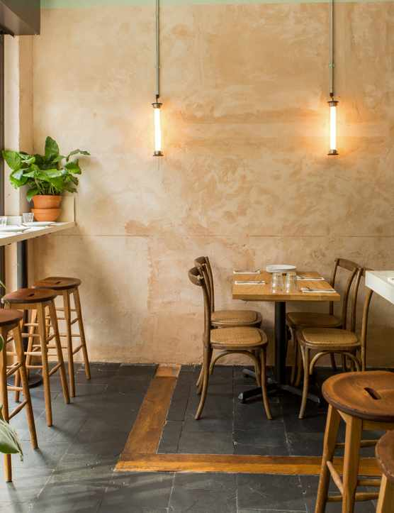 A cosy space with dusty pink walls, palm plants and bar stools