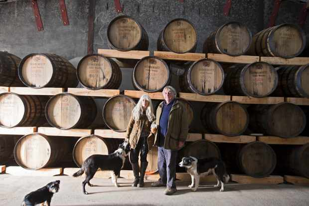 Two people and three dogs stood in front of casks filled with cider