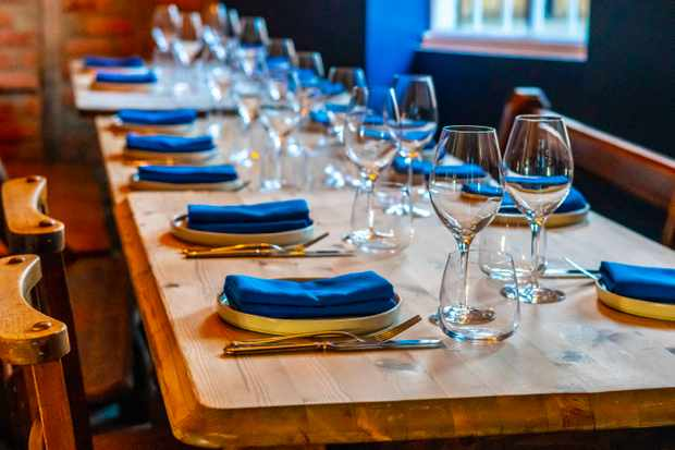 A wooden table laid with crockery, glasses and blue napkins