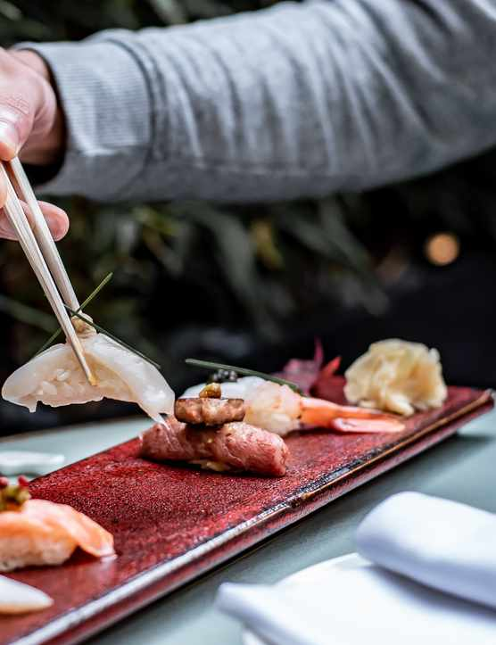 A man picking up sushi with chopsticks at Dinings London
