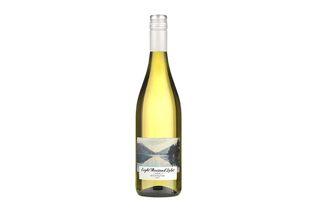 A long bottle of white wine with a label on the front which depicts a serene lake with trees and mountains