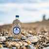 A bottle of Fishers gin on a pebbly beach