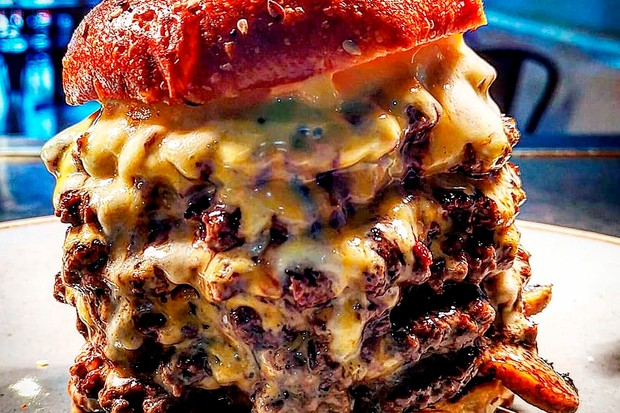 Multiple burgers stacked on top of each other with sauce pouring down over the top