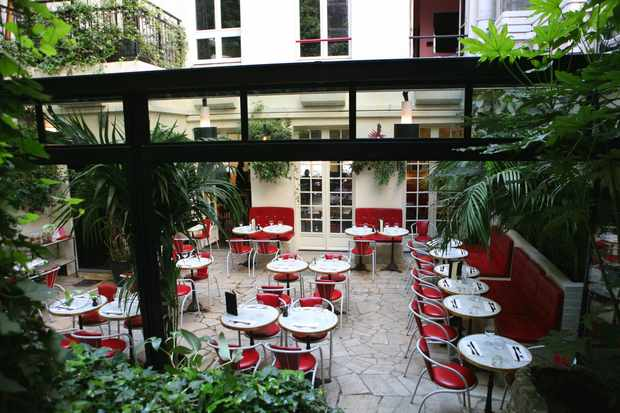 A courtyard garden with tables, red chairs and green plants
