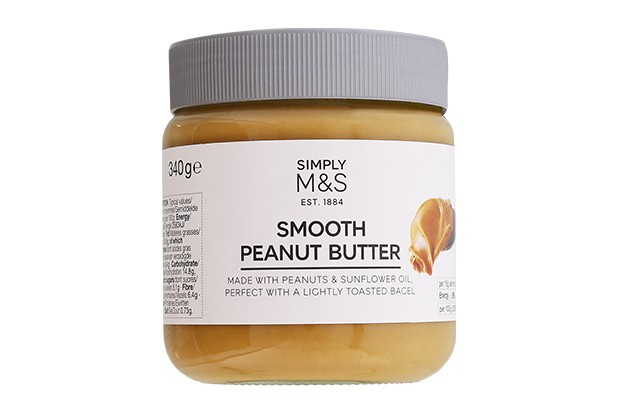 A clear tub filled with brown peanut butter and a grey lid