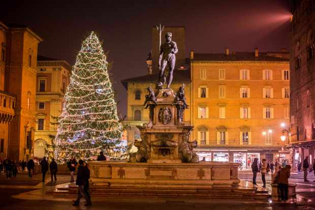 A town square with a Christmas tree with lights on
