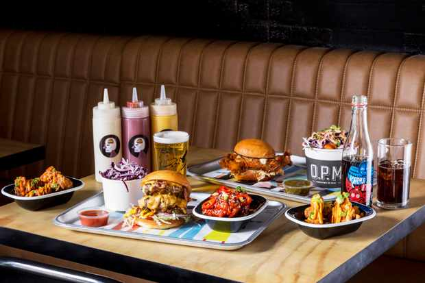 A table with trays on with burgers, chips, dips and bottle of sauce