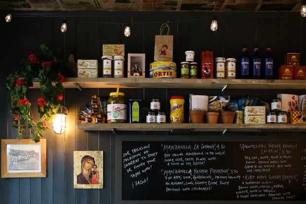 Dark blue panelled walls lined with jars of food and a blackboard with a menu written on in white chalk
