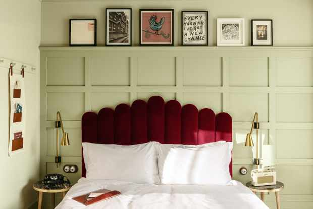 A double bed with red velvet headboard, green panelled walls and pictures