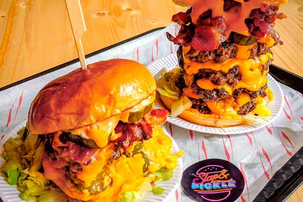 Two burgers on a tray with multiple patties, cheese sauce in glossy buns