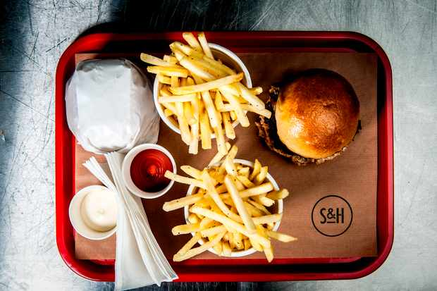 A red tray with a burger and fries on top