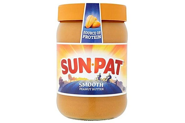 A clear tub filled with brown peanut butter and an orange lid