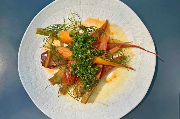 A plate topped with braised carrots and green carrot top pesto