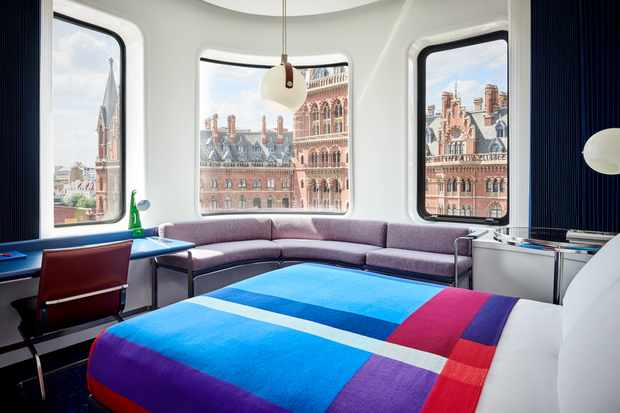 Blue, red and purple bedspreads on bed with view of St Pancras Hotel