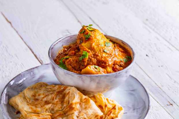 A bowl of chicken with roti bread on the side