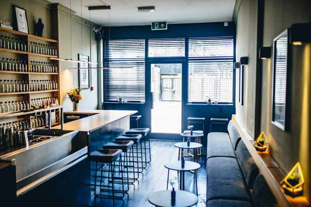 A room with benches, chairs and a bar