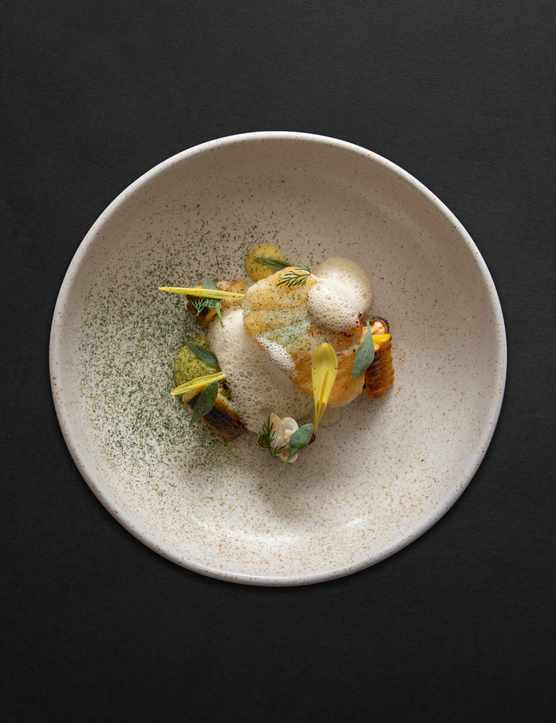 A grey speckled bowl filled with potatoes, foam and sweetcorn