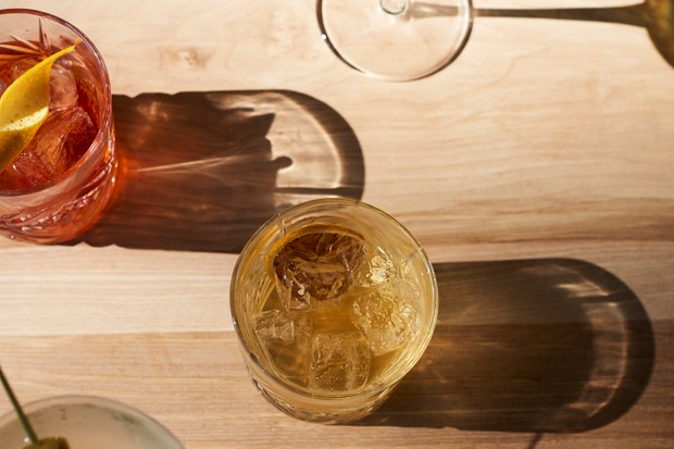 A wooden table topped with cocktails in tumbler glasses