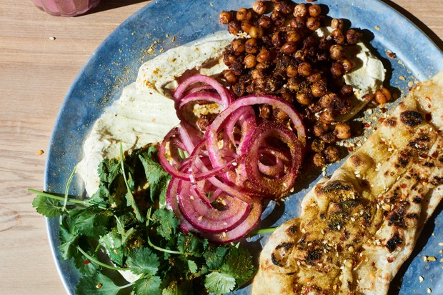 A blue plate topped with a slipper-style flatbread, slices of pink red onions and a sprinkle of crispy golden chickpeas