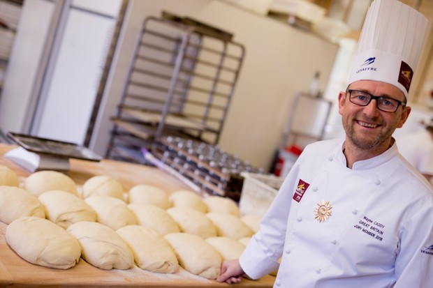 A chef next to a table of raw dough loaves