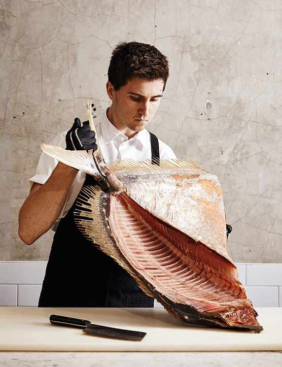 Josh Niland with a whole fish on a wooden board