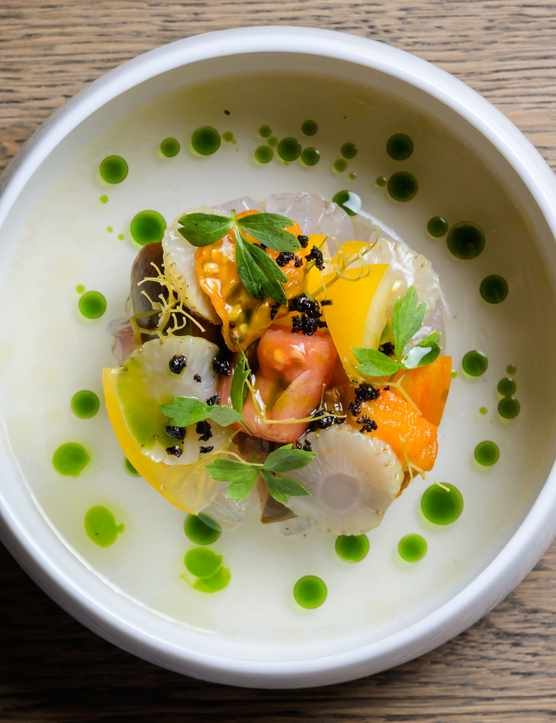 A white plate with cured sea bass and greenery