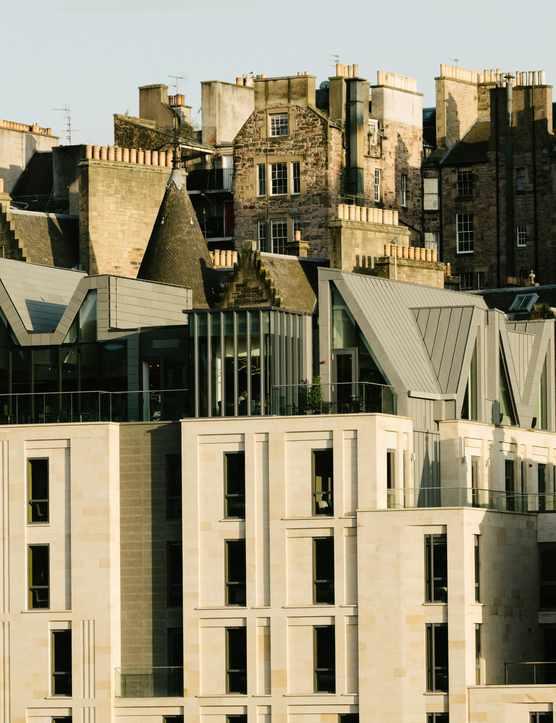A modern white stone building against the Edinburgh skyline