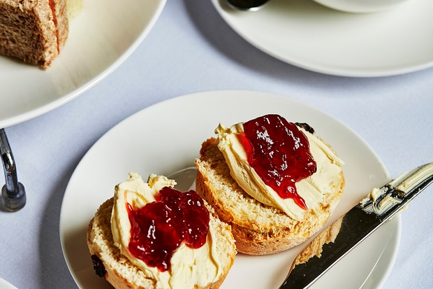 A white plate topped with two halves of a scone, each topped with cream and red jam
