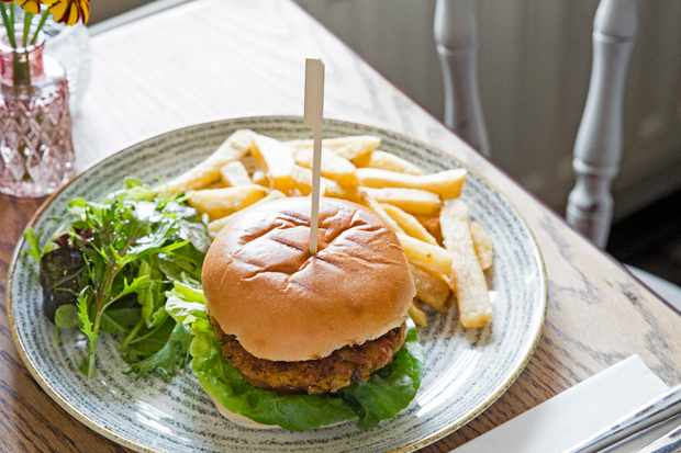 A burger in a golden bun with green leaves and chips on the side