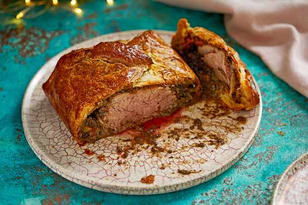 A speckled plate with a golden beef wellington on top