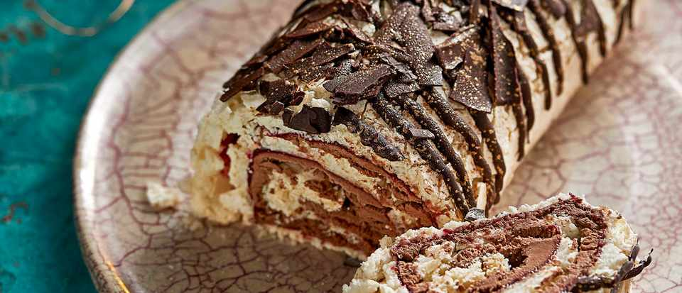 A meringue roulade covered in dark chocolate drizzle
