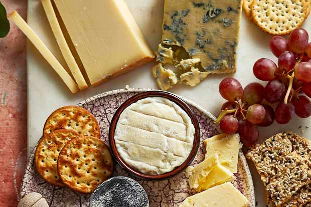 A board topped with chunks of cheese and grapes
