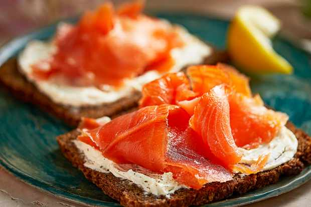 A piece of bread with orange smoked salmon on top