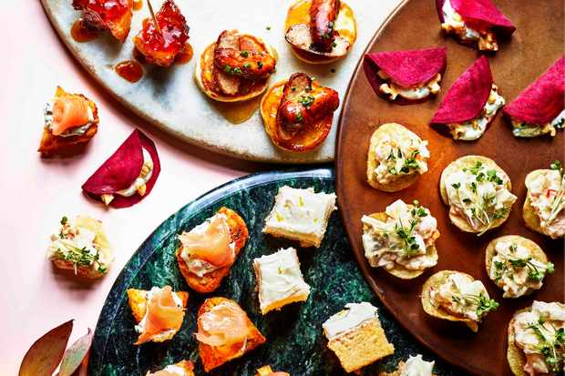 A selection of Christmas canapes on three plates including sausage blinis, gin and tonic cake squares and beetroot tacos
