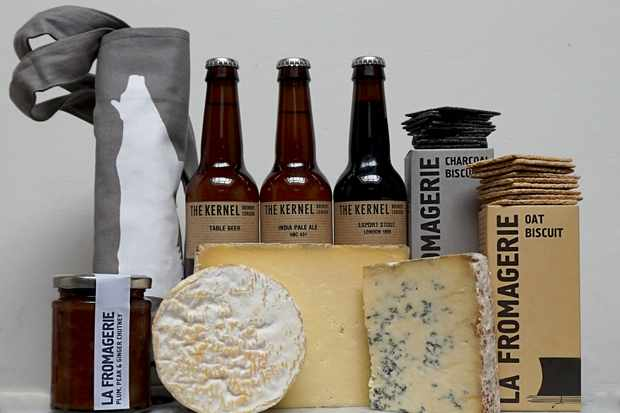 Three large pieces of cheese with bottles of beer and a box of crackers
