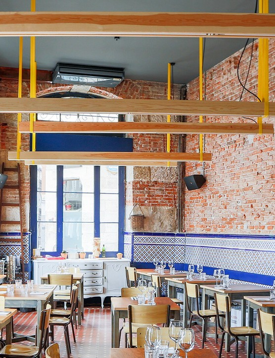 A large dining room with exposed brickwork, blue tiled and lots of table and chairs scattered around the room