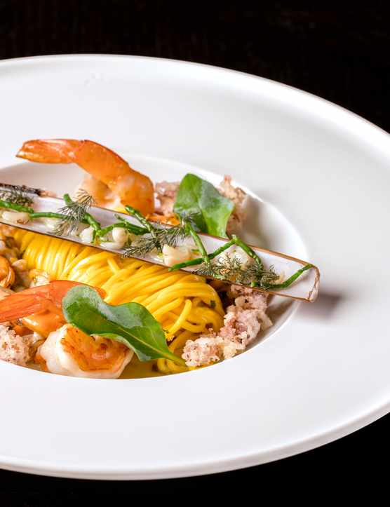 A white plate with yellow linguine pasta and fish