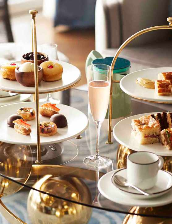 Two cake stands on a glass table filled with cakes and sandwiches