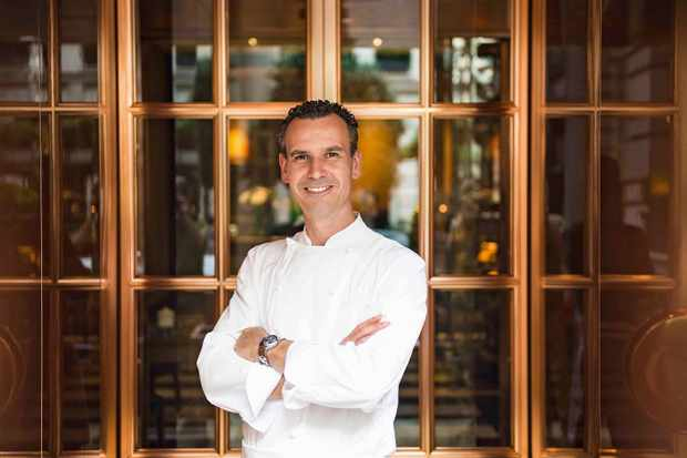 A man in chefs whites stood smiling with his arms folded