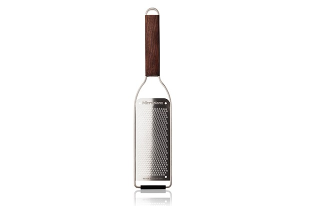 A silver cheese grater with dark wooden handle