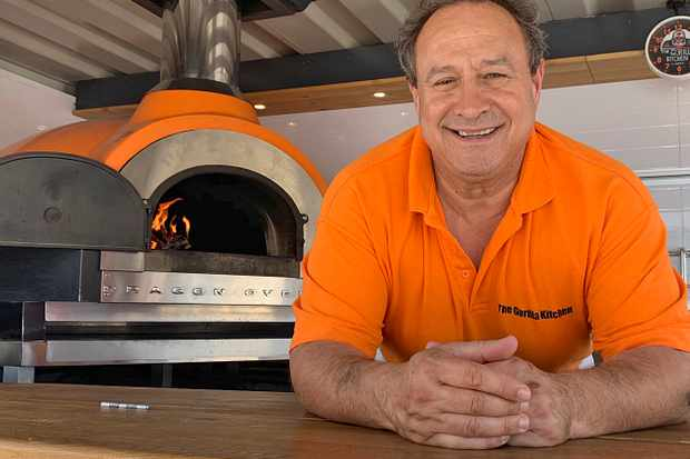 A man wearing an orange tshirt stood with a pizza oven in the background