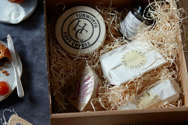 A wooden crate filled with cheese wrapped in white paper