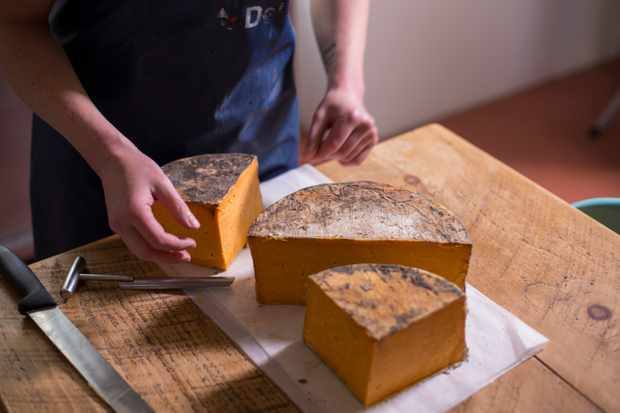 A block of red cheese being cut into