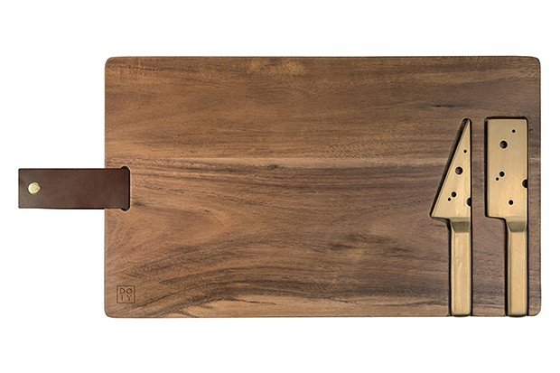 A rectangular wooden cheese board with gold cheese knife in