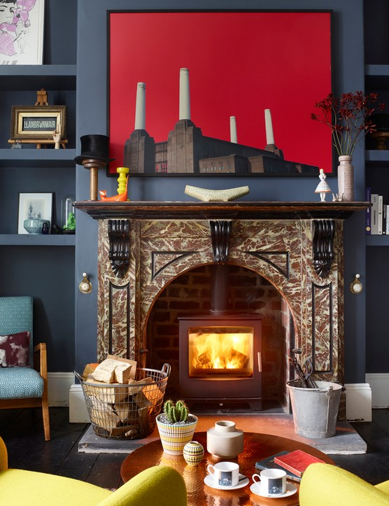 A blue lounge with a roaring fire and yellow armchairs