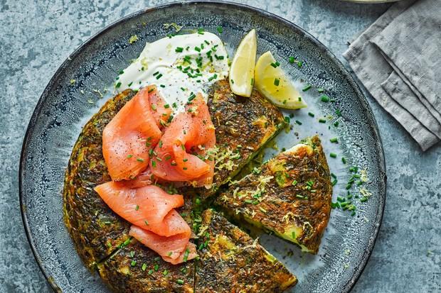 Une assiette bleue surmontée d'une tortilla verte et de tranches de saumon fumé